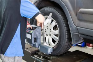 Mechanic fixing the wheel alignment device onto a car wheel. Focus is on the car wheel and wheel alignment device.